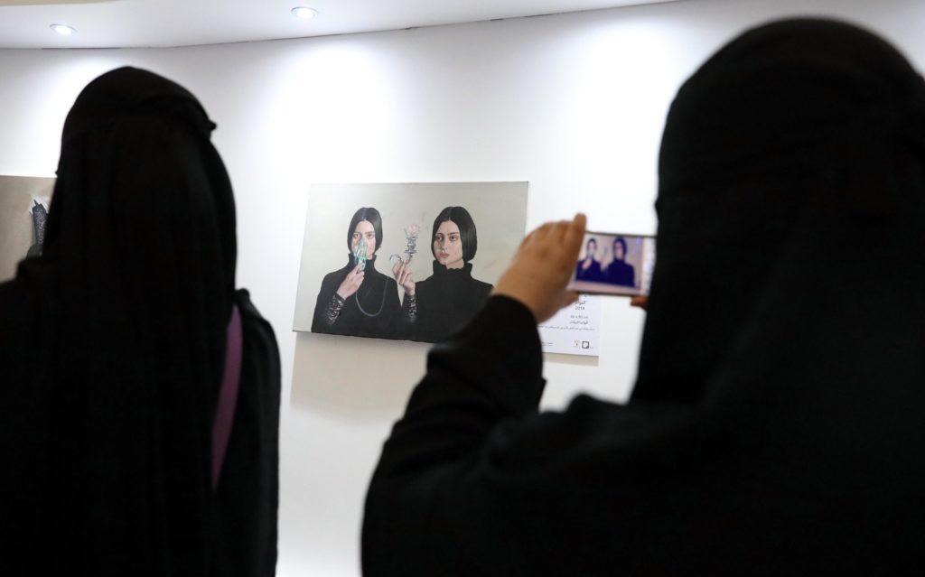 Donne saudite fotografano le opere dell'artista Sabah Al-Dhafiri durante un'esposizione a Riad, Arabia Saudita, 16 febbraio 2018. Epa/Amel Pain