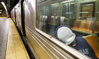 epa08401223 A man sleeps on an empty subway car at the end of the A line at the 207th Street station in New York, New York, USA, on 04 May 2020. New York City is still considered the epicenter of the coronavirus outbreak in the United States and the city's transit system, where ridership is down by 90%, will begin the unusual measure of shutting down overnight for heavy disinfecting as the city tries to mitigate the risk of infection and handle the large number of the homeless who are sleeping in the subways. EPA/JUSTIN LANE