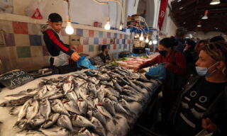 epa09132581 A Tunisian man sells fish on the first day of the Muslim holy month of Ramadan at a market in Tunis, Tunisia, 13 April 2021. Muslims began observing the dawn-to-dusk fast for the holy month of Ramadan across many parts of the Middle East on Tuesday 13 April. to draw worshippers closer to God through sacrifice, remembrance and heightened spirituality.  EPA/MOHAMED MESSARA