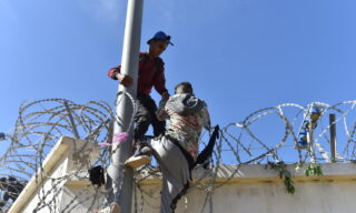 epa09210804 Migrants climb the fence in the northern town of Fnideq in an attempt to cross the border from Morocco to the Spanish enclave of Ceuta, in North Africa 18 May 2021.  In little over 24 hours a total of almost 8,000 people entered into the Spanish city of Ceuta, located in the North African coast, by sea side and hundreds of migrants continue to attempt doing so. The Spanish authorities have deployed the army to patrol on the border separating Ceuta in the Spanish side from the Moroccan side, in a bid to control this latest surge of entry attempts.  EPA/JALAL MORCHIDI
