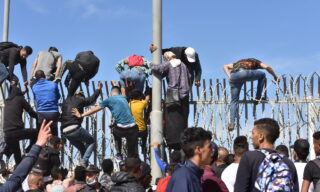 epa09210801 Migrants climb the fence in the northern town of Fnideq in an attempt to cross the border from Morocco to the Spanish enclave of Ceuta, in North Africa 18 May 2021.  In little over 24 hours a total of almost 8,000 people entered into the Spanish city of Ceuta, located in the North African coast, by sea side and hundreds of migrants continue to attempt doing so. The Spanish authorities have deployed the army to patrol on the border separating Ceuta in the Spanish side from the Moroccan side, in a bid to control this latest surge of entry attempts.  EPA/JALAL MORCHIDI