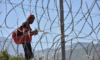 epa09209507 A migrant waits to sneak through the fence in the northern town of Fnideq in an attempt to cross the border from Morocco to the Spanish enclave of Ceuta, in North Africa, 18 May 2021.  At least 5,000 migrants, an unprecedented influx in Spanish authorities said a period of high tension between Madrid and Rabat crept into Ceuta on 17 May, a record for a day. They reached the coast by swimming or walking at low tide from beaches a few kilometers to the south, some using inflatable swimming rings.  EPA/JALAL MORCHIDI