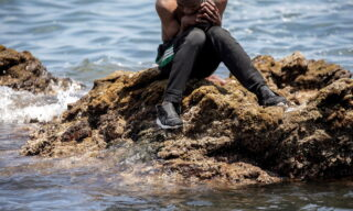 epa09209429 A migrants sits on a rock after crossing the border of Tarajal in Ceuta, Spain, 18 May 2021. On the night of 17 May, a total of 5,000 Moroccan nationals entered into the Spanish city of Ceuta, loacted in the North African coast, by sea side and hundreds of migrants continue to attempt doing so. The Spanish authorities have deployed the army to patrol on the border separating Ceuta in the Spanish side from the Moroccan side, in a bid to control this latest surge of entry attempts.  EPA/BRAIS LORENZO