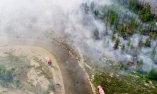 epa09356872 A handout photo made available by the Russian Emergency Ministry on 21 July 2021, shows firefighters working to extinguish the wildfire in the Republic of Sakha (Yakutia), Russia, 21 July 2021. According to the operational data of Russian Emergency ministry, 216 wildfires are active on the territory of the Republic of Sakha (Yakutia). 2,119 people and 297 pieces of equipment were involved in extinguishing forest fires in Yakutia.  EPA/RUSSIAN EMERGENCIES MINISTRY HANDOUT  HANDOUT EDITORIAL USE ONLY/NO SALES