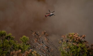 epaselect epa09203442 A helicopter flies over the Palisades Fire burning towards a hiking trail in Topanga, California, USA, 15 May 2021. The fire had burned over 700 acres by nightfall, prompting evacuations.  EPA/Christian Monterrosa